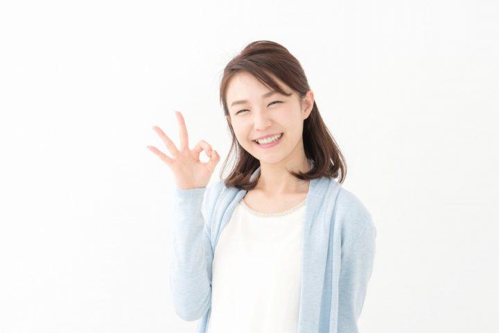 指でOKサインを作って笑顔の女性