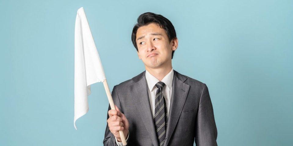 白旗を上げる男性